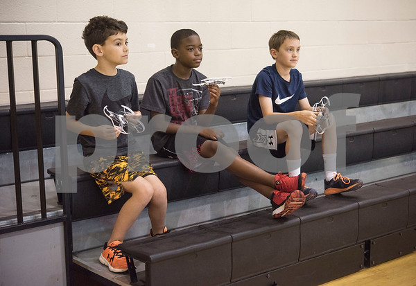 Chuck Weber, 8, Jamal Logan, 10, and John Jordan, 9, sit with miniature drones waiting for an obstacle course to be set up during Drone Adventures, a summer camp held at Tyler Junior College on Wednesday June 6, 2018. Drone Adventures will be held again from July 16-20.  (Sarah A. Miller/Tyler Morning Telegraph)