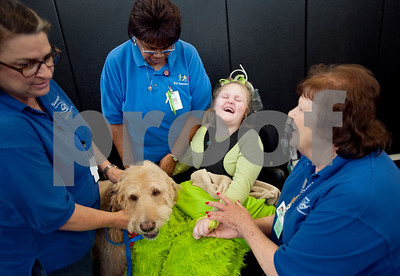 photo by Sarah A. Miller/Tyler Morning Telegraph   Boshears student Kaelan Klostermeier pets Therapet dog Murray with assistance from Therapet volunteers Wendy Gerard, left, Rita Hull, right, and school assistant Minnie Garrett, center, during class Thursday June 26, 2014 at the school in Tyler. Therapet Animal Assisted Therapy partners with the Wayne D. Boshears Center for Exceptional Programs by bringing its animals to the school and working with the students who have varying special needs.