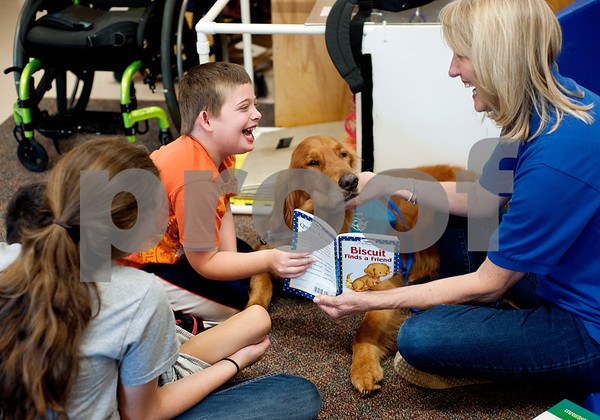 photo by Sarah A. Miller/Tyler Morning Telegraph  Therapet volunteer Susan Strawn and dog Concho read a book with Boshears student Nicholas Goodwin, 7, during class Thursday June 26, 2014 at the school in Tyler. Therapet Animal Assisted Therapy partners with the Wayne D. Boshears Center for Exceptional Programs by bringing its animals to the school and working with the students who have varying special needs.