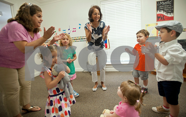 Marsha Trifilio, left, and Mireya Hicks, center, teach students Canela Newberry, 2, Ashley Jones, 4, Emma Vickers, 3, Braxton Jones, 3, and Nolan Newberry Spanish at Early Steps Bilingual Academy in Tyler Tuesday July 7, 2015. Early Steps Bilingual Academy is a Spanish immersion day care for children ages 18 months to five years old. Owners Mireya Hicks and Marsha Trifilio use a variety of activities to teach English-speaking to learn to speak Spanish.  (photo by Sarah A. Miller/Tyler Morning Telegraph)