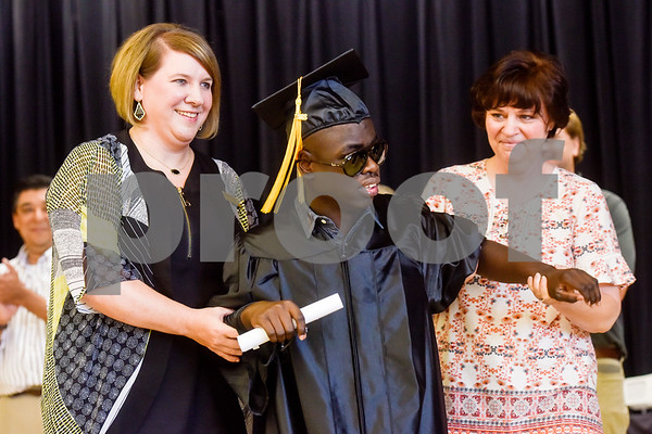 Director Brooke Parker, left, and Diana Garen, right, assist Bryan Ashton Jackson-Pinke as he walks across the stage after receiving his diploma during a graduation ceremony at Wayne D. Boshears Center for Exceptional Programs School in Tyler, Texas, on Thursday, July 19, 2018. (Chelsea Purgahn/Tyler Morning Telegraph)