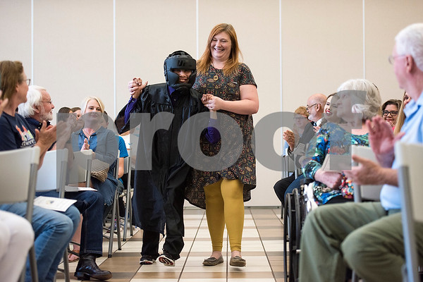 Martin Martinez Allen walks to his seat with Kimberly Lobo as people applaud during a graduation ceremony for Wayne D. Boshears Center for Exceptional Programs at Wayne D. Boshears Center in Tyler, Texas, on Thursday, July 20, 2017. Five students graduated from the program. (Chelsea Purgahn/Tyler Morning Telegraph)