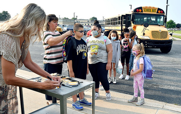 Teachers and staff members fill out bus tags and attach them to the students back backs so they'll find the right bus going home as they get off their school buses at Eastside Elementary School Wednesday morning on the first day of school for ACS.