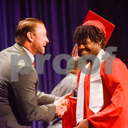 Robert E. Lee principal Dan Crawford and Tradarrius Dunn smile and shake hands during Tyler ISD's summer graduation at Caldwell Auditorium in Tyler, Texas, on Friday, Aug. 10, 2018. (Chelsea Purgahn/Tyler Morning Telegraph)