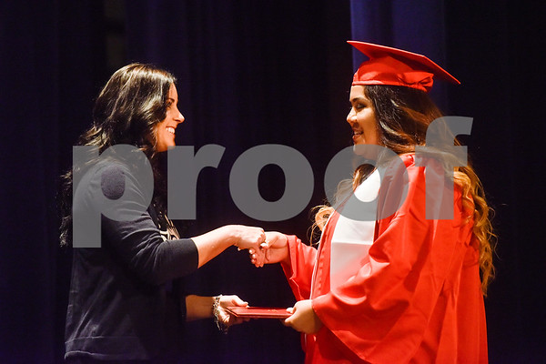 A woman smiles as she shakes Nayeli Barrios' hand and gives her her diploma during Tyler ISD's summer graduation for John Tyler High School, Robert E. Lee High School and Rise Academy at Caldwell Auditorium in Tyler, Texas, on Friday, Aug. 10, 2018. (Chelsea Purgahn/Tyler Morning Telegraph)