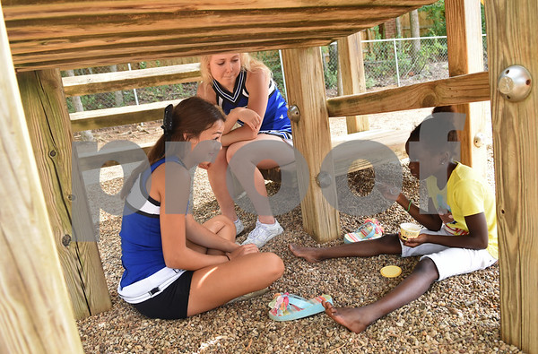 Grace Community School cheerleaders Carly Furqueron and Sara Billings talk with second grader Addy Powell, 8, as she eats ice cream under the playground equipment Saturday August 13, 2016 during the kindergarten picnic at the elementary school. Powell attended with the event with her younger sibling.   (Sarah A. Miller/Tyler Morning Telegraph)
