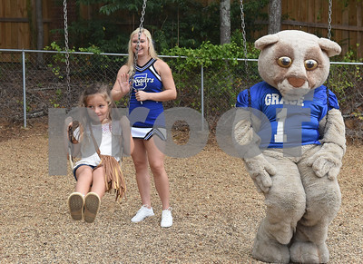 Junior kindergartener Paisley Mink, 5, swings next to mascot Champ with help from Grace Community School cheerleader Jaycie Wilson during the junior kindergarten popsicle playdate Saturday August 13, 2016. The annual event was held to familiarize the new young students with their school, classmates and teachers. Classes begin Wednesday for Grace Community School.  (Sarah A. Miller/Tyler Morning Telegraph)