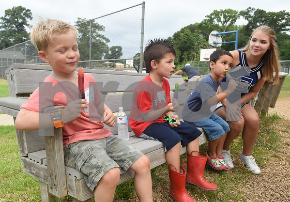 Junior kindergarteners Rohen Sadler, 4, Elliot Graham, 4, and Evan Serrato, 4, eat popsicles with cheerleader Emma Winebarger at the Grace Community School junior kindergarten popsicle playdate Saturday August 13, 2016. The annual event was held to familiarize the new young students with their school, classmates and teachers. Classes begin Wednesday for Grace Community School.  (Sarah A. Miller/Tyler Morning Telegraph)