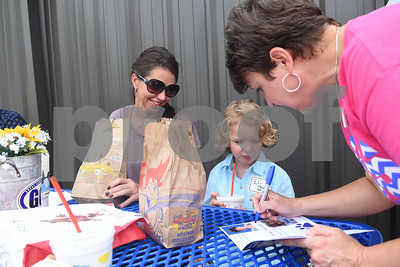 Shawnee Murphy watches as her son Eli Murphy, 6, gets an autograph from Grace Community School elementary assistant Lisa Provines during the kindergarten picnic Saturday August 13, 2016. The annual kindergarten picnic was held to familiarize the new young students with their school, classmates and teachers. Classes begin Wednesday for Grace Community School.  (Sarah A. Miller/Tyler Morning Telegraph)
