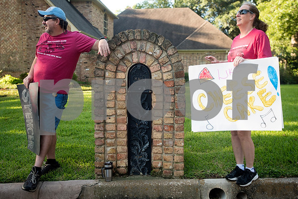 John and Mickie Webb hold signs to support the band during Robert E. Lee Red Raider Band's March-A-Thon in Tyler, Texas, on Saturday, Aug. 19, 2017. The seventh annual March-A-Thon is the band's largest fundraiser and takes the entire band through neighborhoods to play street concerts for donations. (Chelsea Purgahn/Tyler Morning Telegraph)