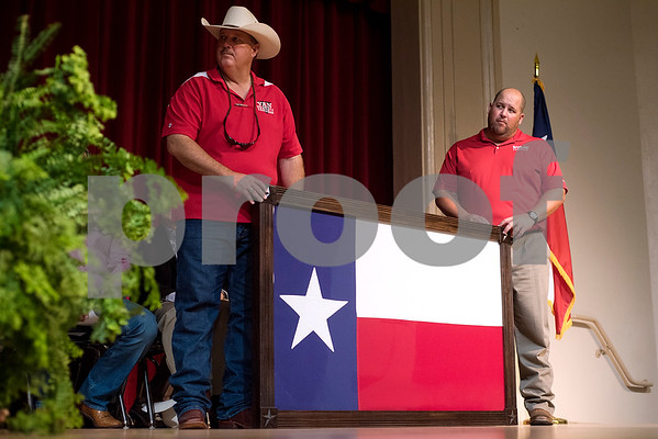 Two men hold a framed Texas flag that once flew over the state Capitol that was donated by a state elected official to Van ISD during a grand opening ceremony for J.E. Rhodes Elementary School in Van, Texas, on Saturday, Aug. 19, 2017. The elementary school was rebuilt after it was demolished in May 2015 due to a tornado. (Chelsea Purgahn/Tyler Morning Telegraph)