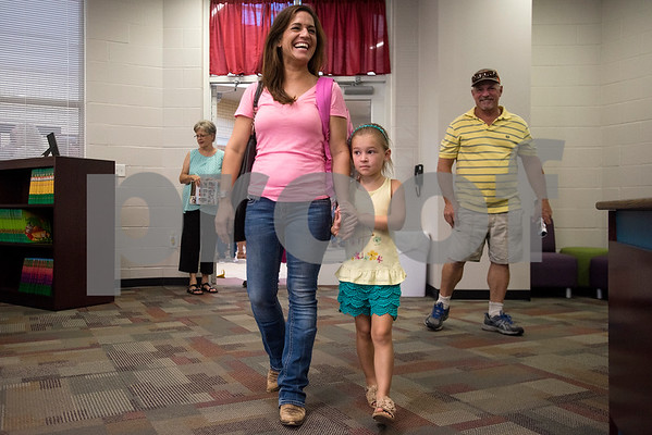 Laura Stephenson smiles as she walks into the new school library with her daughter Everli Wells, who will be in kindergarten this year, during a grand opening ceremony for J.E. Rhodes Elementary School in Van, Texas, on Saturday, Aug. 19, 2017. The elementary school was rebuilt after it was demolished in May 2015 due to a tornado. (Chelsea Purgahn/Tyler Morning Telegraph)