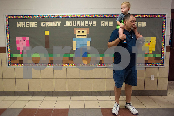 John Wilson holds Austin Wilson, 2, on his shoulders as they check out the new school during a grand opening ceremony for J.E. Rhodes Elementary in Van, Texas, on Saturday, Aug. 19, 2017. The elementary school was rebuilt after it was demolished in May 2015 due to a tornado. (Chelsea Purgahn/Tyler Morning Telegraph)