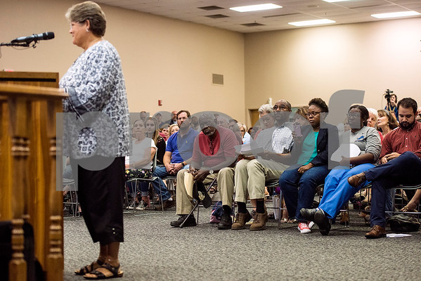 People listen as a woman speaks during a Tyler ISD board meeting in Tyler, Texas, on Monday, Aug. 21, 2017. Residents came to discuss changing the name of Robert E. Lee High School, with the discussion being fueled by protests across the nation regarding Confederate monuments. (Chelsea Purgahn/Tyler Morning Telegraph)