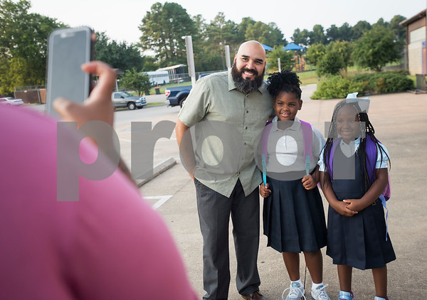 Promise Academy Assistant Principal Samuel Fuentes takes photos with students outside of their new building in Tyler on the first day of school on Thursday Aug. 23, 2018. The school has a new location inside the Boys and Girls Club building, 504 W. 32nd Street.  (Sarah A. Miller/Tyler Morning Telegraph)