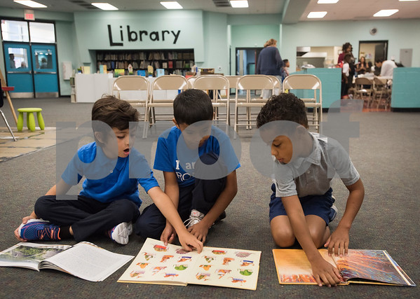 Jose Amaya, 6, Josue Ramirez, 7, and Ryder Mathis, 6, read books before the school assembly at Promise Academy, a private Christian school in Tyler on the first day of school on Thursday Aug. 23, 2018. The school has a new location inside the Boys and Girls Club building, 504 W. 32nd Street.  (Sarah A. Miller/Tyler Morning Telegraph)
