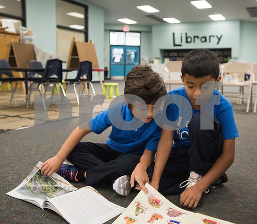 Jose Amaya, 6, and Josue Ramirez, 7, read books before the school assembly at Promise Academy, a private Christian school in Tyler on the first day of school on Thursday Aug. 23, 2018. The school has a new location inside the Boys and Girls Club building, 504 W. 32nd Street.  (Sarah A. Miller/Tyler Morning Telegraph)