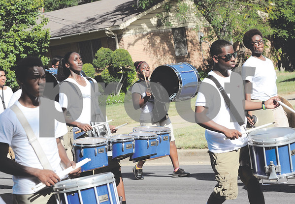 The drumline keeps a steady beat as the band makes its way down Benbrook Drive. (Victor Texcucano/Staff)