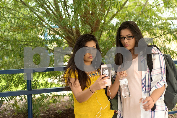 Senior Diana Galindez and her sister sophomore Jade look at Diana's phone during the first day of school at John Tyler High School in Tyler, Texas, on Monday, Aug. 28, 2017. (Chelsea Purgahn/Tyler Morning Telegraph)
