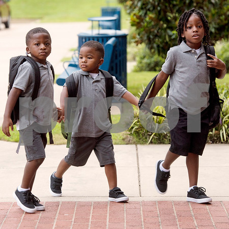 Brothers Dsavious, 5, Dayvion, 4, and Daviare Sueing, 6, hold hands as they walk into school together during the first day of school at Orr Elementary School in Tyler, Texas, on Monday, Aug. 28, 2017. (Chelsea Purgahn/Tyler Morning Telegraph)