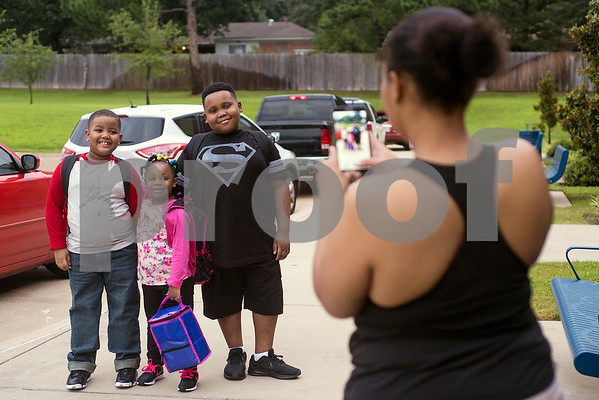 Ivan Blake Jr., 7, Sherticia Dean, 5, and John Dean, 9, pose for a photo as Karen Dean takes their picture during the first day of school at Orr Elementary School in Tyler, Texas, on Monday, Aug. 28, 2017. (Chelsea Purgahn/Tyler Morning Telegraph)