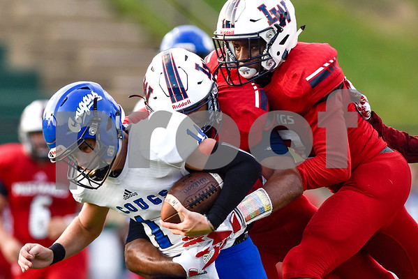 Grace Community School quarterback Braydon Stone (14) is tackled by Waxahachie Life players during a high school football game at McCallum Stadium at Bishop T.K. Gorman Catholic School in Tyler, Texas, on Thursday, Aug. 31, 2017. The Grace Community School Cougars beat the Waxahachie Life Mustangs 48-28. The Grace Community School Cougars beat the Waxahachie Life Mustangs 48-28. (Chelsea Purgahn/Tyler Morning Telegraph)