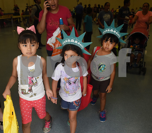 Elanie Ramirez, 5, Cynthia Ramirez, 5, and Galilea Ramirez, 5, attend the School is Cool event Thursday August 4, 2016 at Harvey Convention Center. School is Cool provides free backpacks and school supplies to children as well as free haircuts, immunizations, dental and eye exams.   (Sarah A. Miller/Tyler Morning Telegraph)