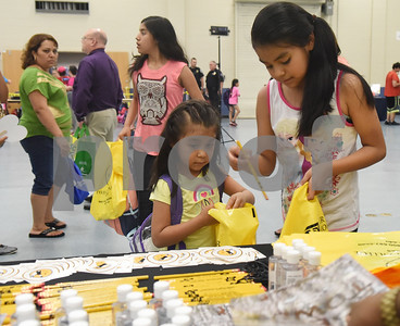 Kayla Valladares, 4, and Jennifer Valladares, 11, get pencils from a Tyler Junior College booth at the School is Cool event Thursday August 4, 2016 at Harvey Convention Center. School is Cool provides free backpacks and school supplies to children as well as free haircuts, immunizations, dental and eye exams.   (Sarah A. Miller/Tyler Morning Telegraph)