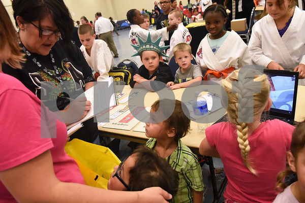 People sign up for Songahm Martial Arts at the annual event called School is Cool Thursday August 4, 2016 at Harvey Convention Center. School is Cool provides free backpacks and school supplies to children as well as free haircuts, immunizations, dental and eye exams.   (Sarah A. Miller/Tyler Morning Telegraph)