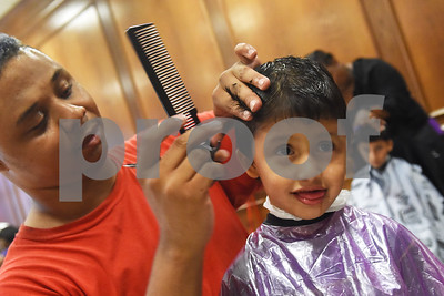 Hair stylist Jeremy Kelly of Star College gives Elias Avalos, 5, a haircut at the annual event called School is Cool. School is Cool provides free backpacks and school supplies to children as well as free haircuts, immunizations, dental and eye exams.   (Sarah A. Miller/Tyler Morning Telegraph)