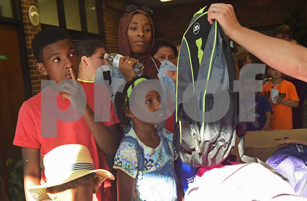 Amina Aguirre watches as her children Yusuf Aguirre, 13, Atiya Aguirre, 5, and Amaya Aguirre, 10, receive free backpacks from the annual event called School is Cool. School is Cool provides free backpacks and school supplies to children as well as free haircuts, immunizations, dental and eye exams.   (Sarah A. Miller/Tyler Morning Telegraph)