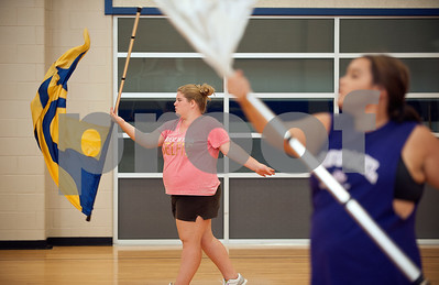 Brownsboro Military Band Auxiliary color guard members freshman Kristen Phillips, left, and senior sergeant Alex Blott, right, practice a routine inside the Brownsboro Elementary School gymnasium Thursday. The marching band, including its drumlin, color guard and majorettes have been participating in band camp this week to prepare for their upcoming football season performances. The band will perform at Brownsboro's first football game at Crandall Aug. 28 and the first home game is Sept. 11.   (photo by Sarah A. Miller/Tyler Morning Telegraph)