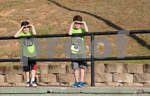 St. Gregory Cathedral School students Preston Watson, 8, and John Louis Nasche, 9, watch runners compete in the 30th annual St. Gregory Fun Run held at the Bishop Thomas K. Gorman campus in Tyler Saturday Sept.  19, 2015. The event is a fundraiser for St. Gregory Cathedral School, Tyler's oldest private, Christian elementary school.  (Sarah A. Miller/Tyler Morning Telegraph)