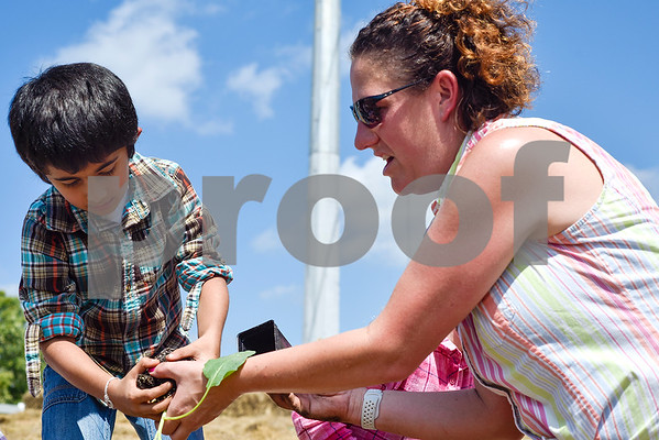 Sohum Shah, 6, holds a plant as lower school science teacher Katie Johnson hands it to him at the Learning Farm at All Saints Episcopal School in Tyler, Texas, on Wednesday, Sept. 20, 2017. The lower school is participating in the upkeep with the garden as part of their science classes. (Chelsea Purgahn/Tyler Morning Telegraph)