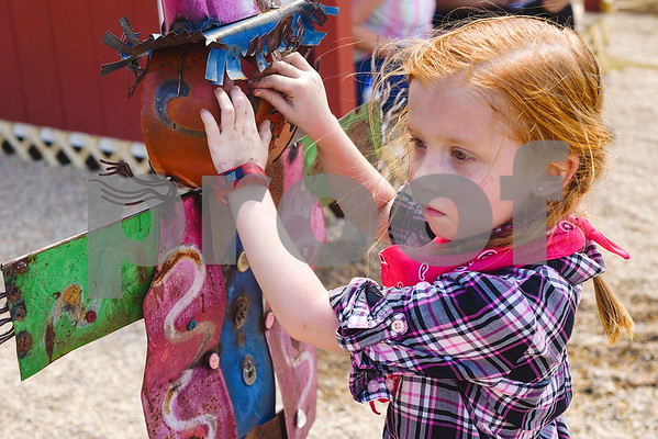 Maclayne Copfei, 6, plays with a metal scarecrow at the Learning Farm at All Saints Episcopal School in Tyler, Texas, on Wednesday, Sept. 20, 2017. The lower school is participating in the upkeep with the garden as part of their science classes. (Chelsea Purgahn/Tyler Morning Telegraph)