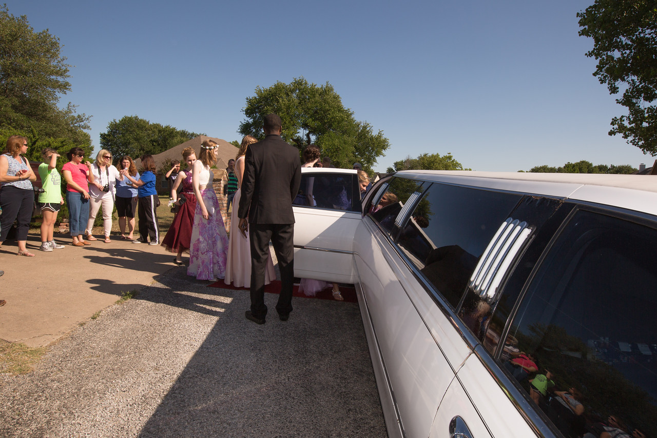 Parents watch as their daughters board a limousine to Promenade at Aledo High School.