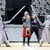 "Don Knight | The Herald Bulletin<br /> Logan Hamilton performs a solo as statues come to life around him in Anderson's show ""The Ghosts of Edinburgh Castle"" during Indiana State Fair Band Day on Saturday. From left, James Long and Noah Green portray the ghostly statues."
