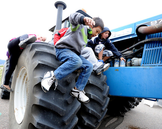 """Cody Xiong of Aspen Creek K-8 School in Broomfield, jumps off a giant Ford Tractor during the farm equipment tour.<br /> Fourth graders from Boulder Valley Schools were able to learn about farms and food at the Arapahoe Campus Farm Day on thursday. For a video and more photos, go to  <a href=""""http://www.dailycamera.com"""">http://www.dailycamera.com</a>.<br /> Cliff Grassmick  / October 4, 2012"""