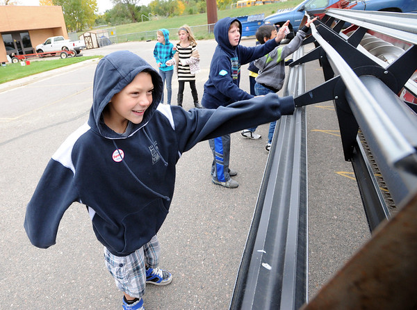 """Chase Kennedy of Aspen Creek K-8 School in Broomfield, spins the blades of the wheat cutter.<br /> Fourth graders from Boulder Valley Schools were able to learn about farms and food at the Arapahoe Campus Farm Day on thursday. For a video and more photos, go to  <a href=""""http://www.dailycamera.com"""">http://www.dailycamera.com</a>.<br /> Cliff Grassmick  / October 4, 2012"""