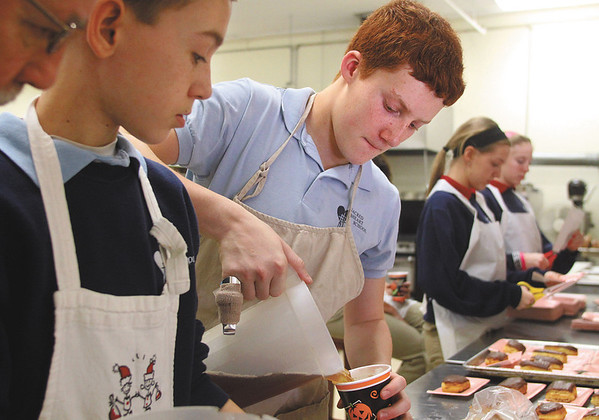 Zach Shelton pours cups of tea as he and other Sacred Heart Catholic School eighth-graders volunteer at the Community Kitchen in Jeffersonville Thursday morning.  More than 180 students from the school fanned out across the community for the school's day of service.  Staff photo by C.E. Branham