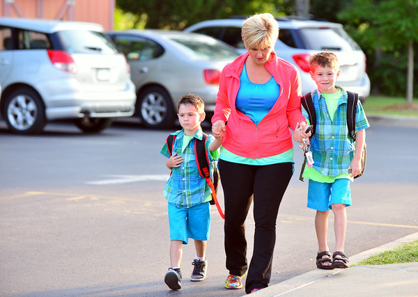 Tonya Cavallo walks with her sons, Chase, 7, and Jack, 5, toward the Grant Line Elementary car-rider entrance for the first day of school Thursday morning in New Albany. <br /> Staff photo by Tyler Stewart