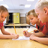 Henryville kindergarten students Natalie Miller, left, Braiden Castillo and Cameron McClendon fill out their seating chart in art class on the first day of class in the rebuilt Henryville schools. Staff photo by C.E. Branham