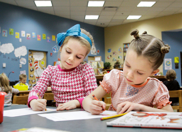 "Ava Hayes, 6, left, and Savannah Allen-Farnsley, 5, sport their Wacky Wednesday attire, as part of Spirit Week, while working on fairy godmother letters after they were read ""Cinder-Elly"" during library at Grant Line Elementary School in New Albany on Wednesday afternoon. Staff photo by Christopher Fryer"