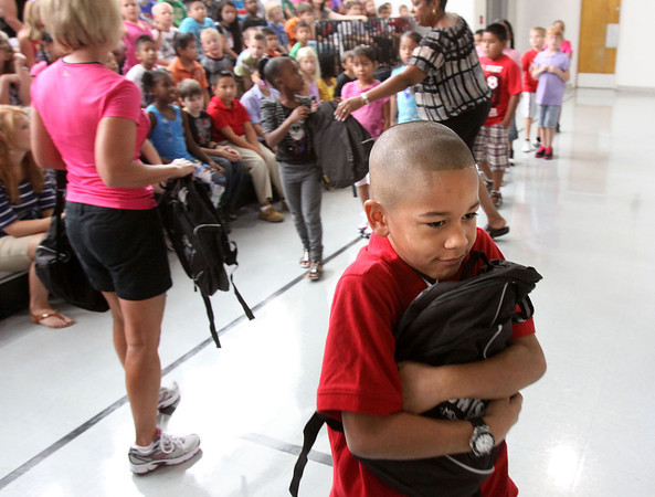 Parkwood Elementary School second-grader Jason Hailstock clutches the new backpack he received Thursday morning at the Clarksville school. All Parkwood students, more than 500, received the backpacks full of school supplies courtesy of MDwise. Staff photo by C.E. Branham