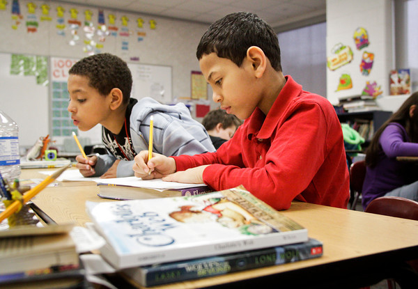 Clarksville Elementary School third-graders Amir Elghailany, 10, right, and Drevon White, 10, work on cursive writing exercises during their class on Thursday morning. Staff photo by Christopher Fryer