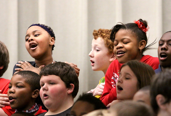 Spring Hill Elementary School students Breanna Sheckles, left, Jeffrey Grisler and Jasmine Walker sing along during the school's Black History Month presentation Wednesday. Staff photo by C.E. Branham