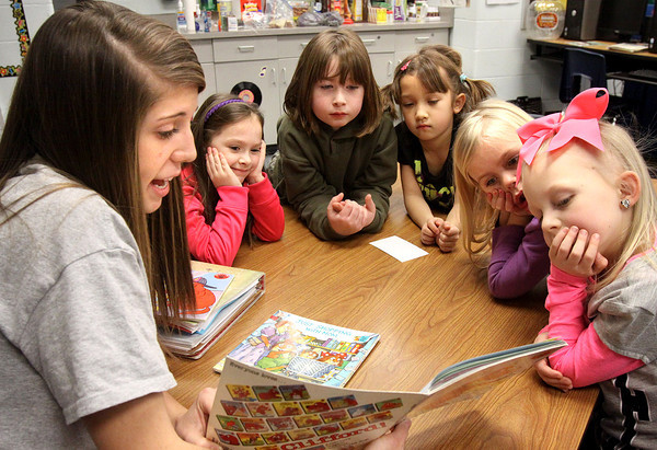 Members of the Jeffersonville High School girls' basketball team helped first graders at Utica Elementary School celebrate the 100th day of school by reading 100 minutes to the students Wednesday afternoon. Taylor Davis, above, reads to a group of students. Staff photo by C.E. Branham