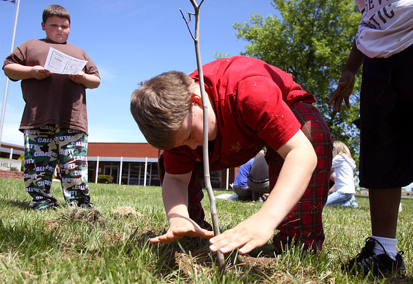 Spring Hill Elementary School fourth-grader Michael Jenkins tamps down loose dirt around a yellowwood tree he and classmates planted at the school Friday. The school planted 10 donated trees total as part of the City of Jeffersonville Arbor Day celebration. Staff photo by C.E. Branham