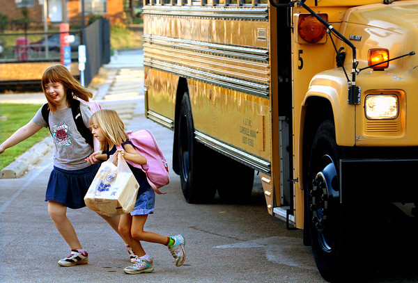Clarksville Elementary School third-grader Willow Martin leads her sister Rowan Martin, a kindergarten student, off the bus as Clarksville Community Schools students returned to class Monday. Staff photo by C.E. Branham