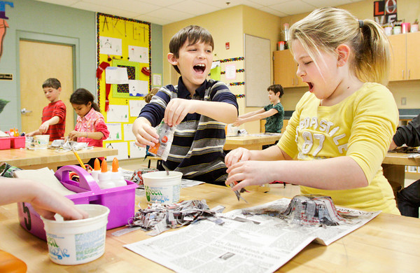Fourth-graders Aidan Davis, left, and Jillian Mifflin goof around while working on their papier-mâché bowls in art class at Grant Line Elementary School in New Albany on Thursday morning. The class will have to wait two weeks for them to completely dry before they can remove the frames and add decorations. Staff photo by Christopher Fryer